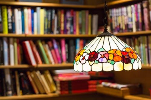 Lampunvarjostimen takaa näkyy kirjoja, joita voi lukea ennen teatteria ja ruokaa syödessä.
